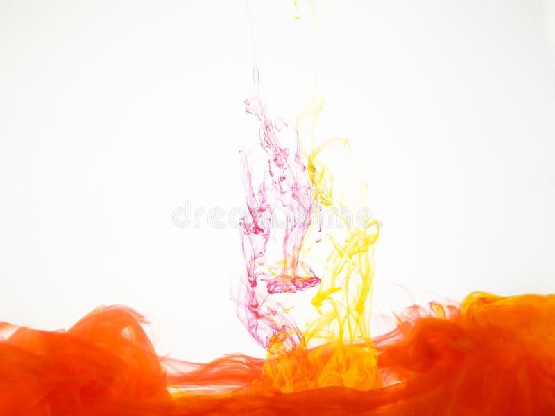 Movimiento abstracto del remolino amarillo-rojo debajo del agua explosión Amarillo-roja de la tinta de acrílico en agua en blanco fotografía de archivo libre de regalías