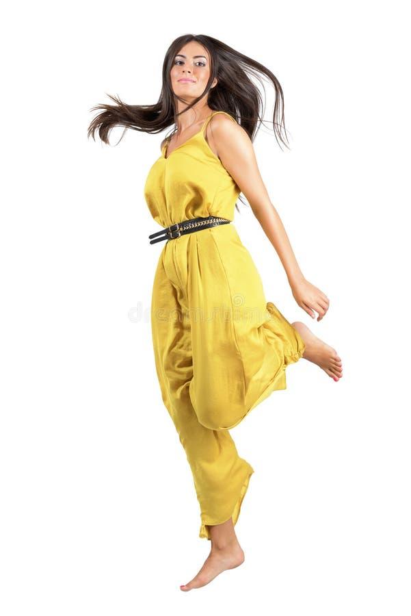 Movimiento congelado de la mujer hermosa joven en el salto amarillo del mono foto de archivo
