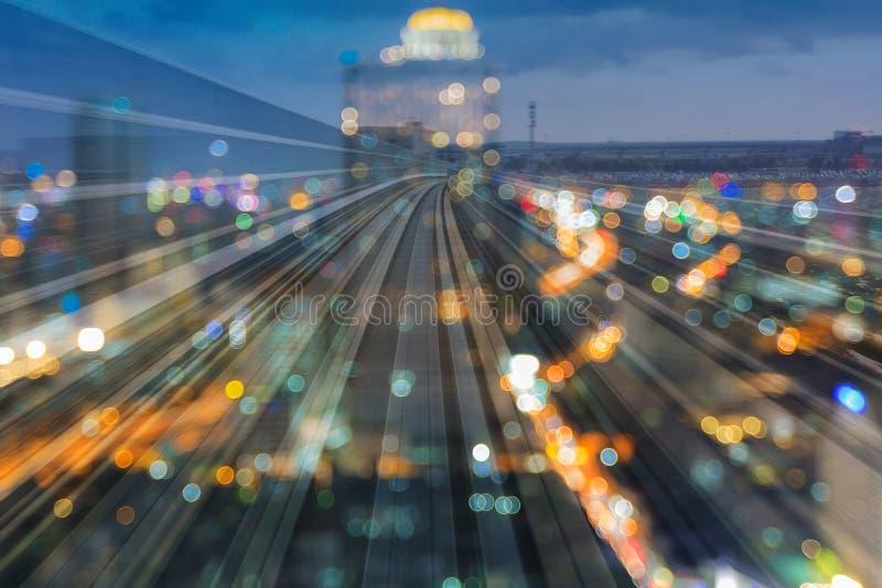 Movimiento crepuscular de la vía del tren de la exposición del doble de la luz de la falta de definición de la ciudad en el centr imágenes de archivo libres de regalías