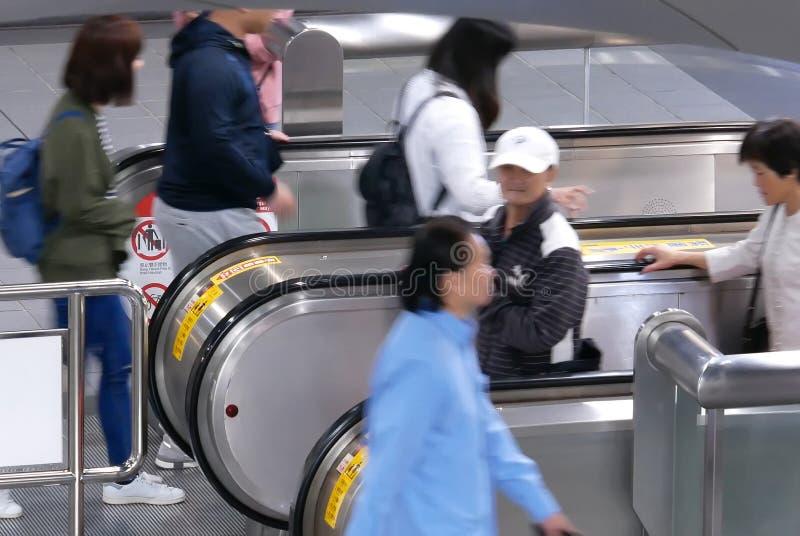 Movimiento de los viajeros que llevan la escalera móvil para ir la plataforma del MRT durante hora punta en Taipei Taiwán imagen de archivo