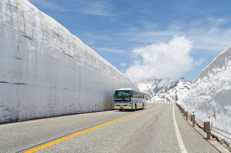 Movimiento del autobús de turistas a lo largo de la pared de la nieve de las montañas de Japón en la ruta alpina del kurobe de ta fotos de archivo