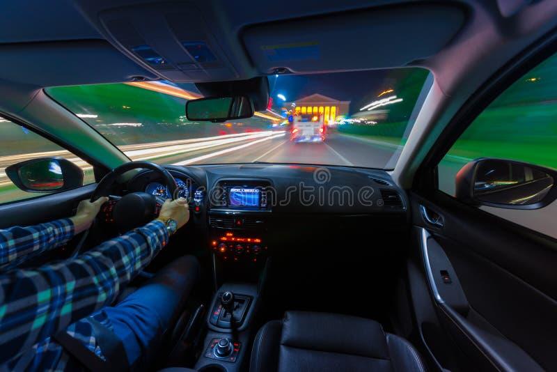 Movimiento del coche en la noche en una opinión de la velocidad del camino interior, brillante con las luces con un coche en la v imagenes de archivo