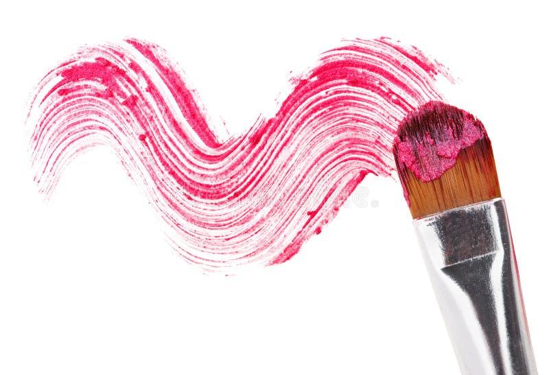 Movimiento rosado del lápiz labial (muestra) con el cepillo del maquillaje foto de archivo libre de regalías