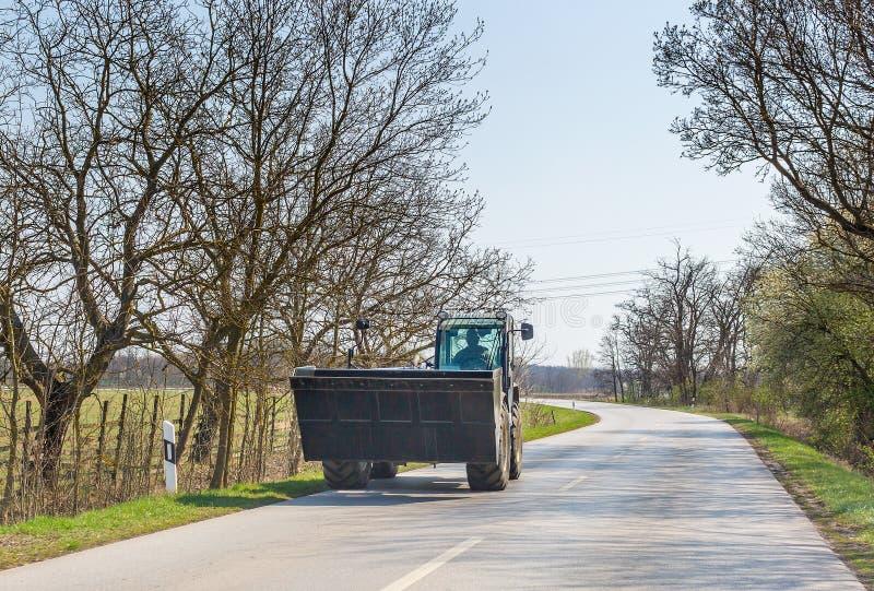 Movimientos del excavador en la carretera de asfalto fotos de archivo libres de regalías