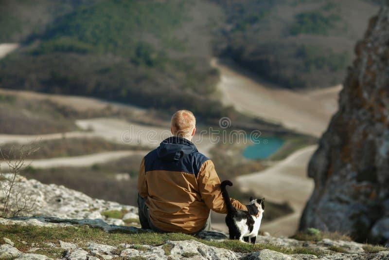 Movimientos del hombre un gato blanco y negro en la cuesta de la montaña fotos de archivo