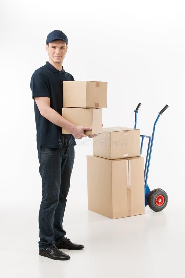 Moving коробки. Во всю длину молодого работника доставляющего покупки на дом держа стог o стоковые изображения