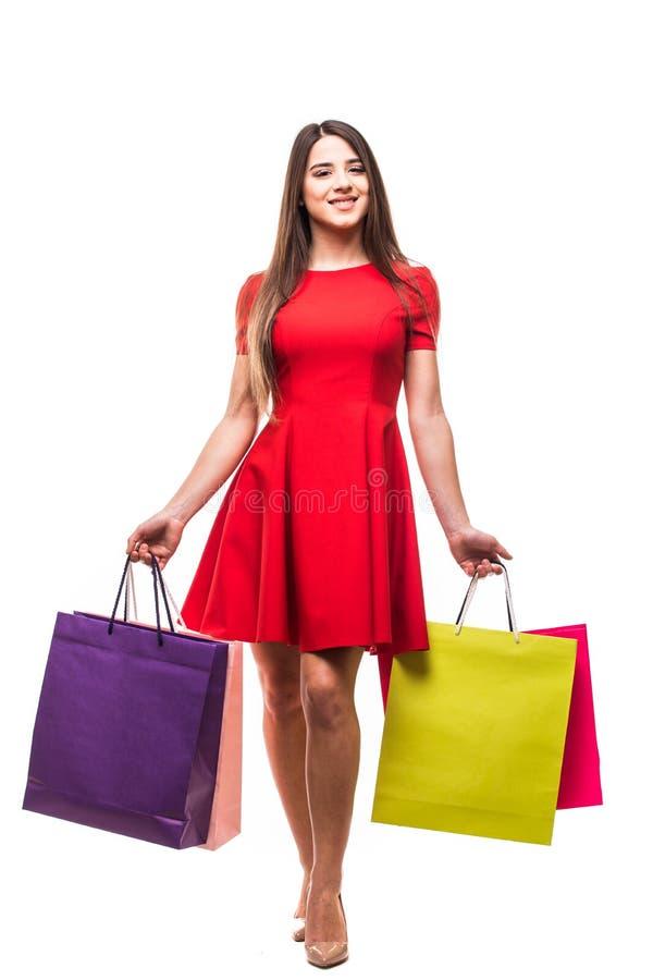 Moving молодая женщина с сумками, ходя по магазинам концепция, изолированная на белой предпосылке стоковая фотография