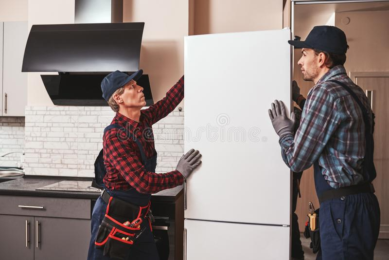 Moving again. Young men mechanics moving refrigerator stock photos
