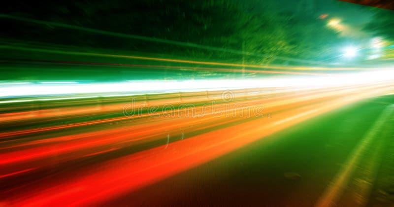 Moving bilar med den snabba suddighet trailen av billyktor royaltyfri foto