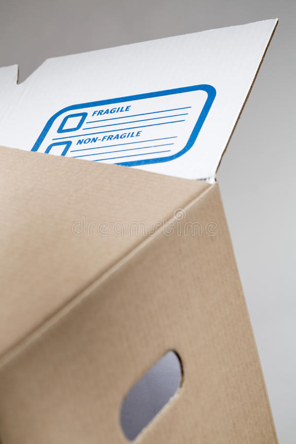 Moving Box with Fragile Label. Closeup image of a fragile marking label on a storage or moving carton box stock images