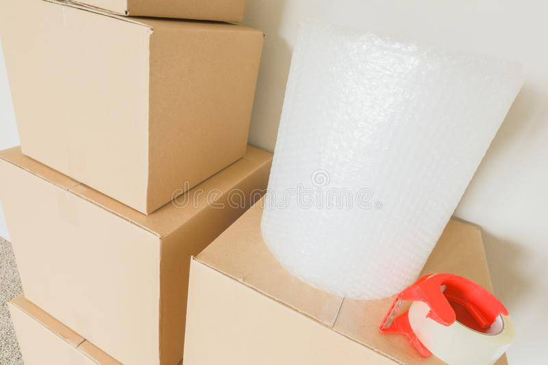 Moving Boxes and Packing Tape In Empty Room. Variety of Packed Moving Boxes with Materials In Empty Room Against Wall stock image