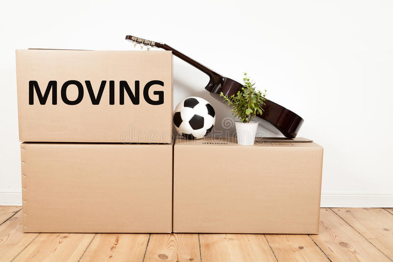 Moving boxes in room. Moving boxes, guitar, flower and footall stock photo