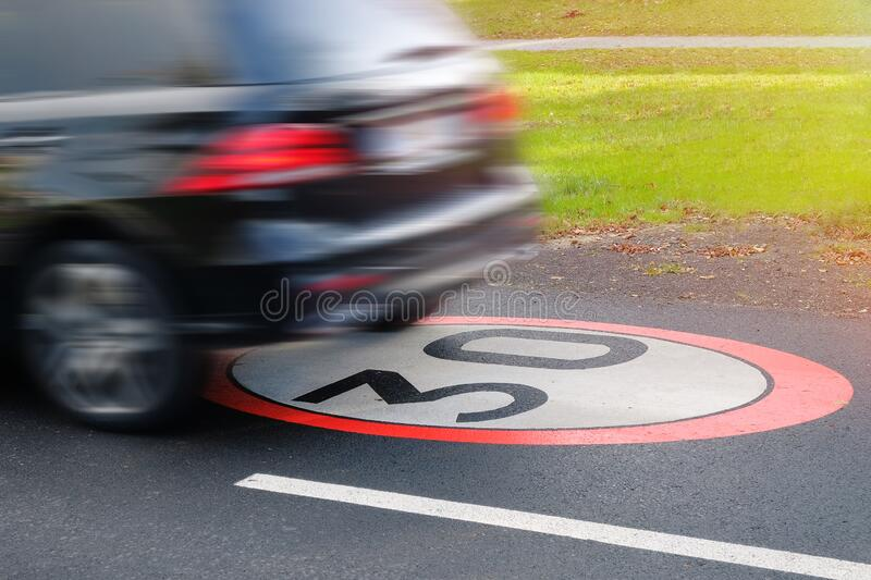 A moving car in violation of traffic rules, limiting the maximum speed to 30.  stock image
