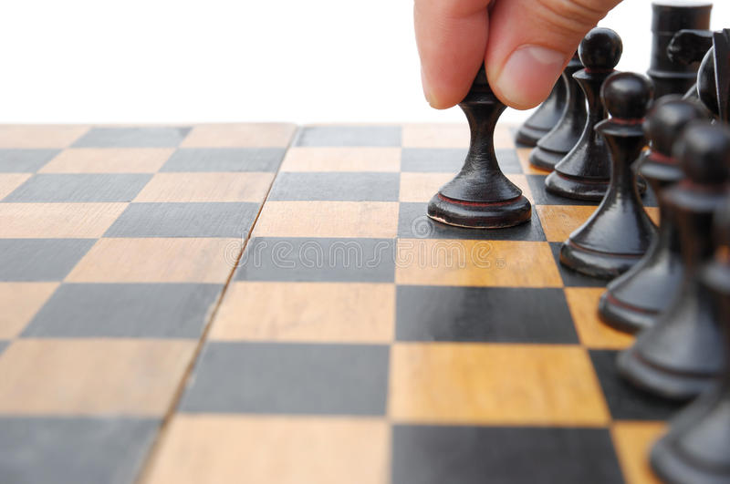 Moving a chess. Man's hand moving a chess stock photo