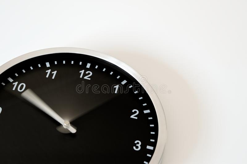 Moving clock hand of the black wall clock. Clock hand is moving from ten to ten till 5 past ten. Black wall clock on white background stock image