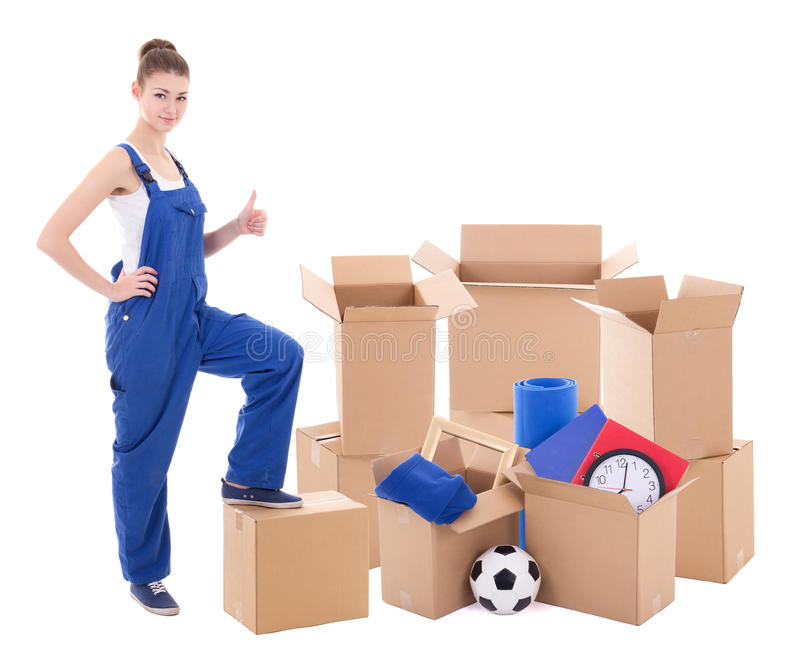 Moving day concept - young woman in blue workwear with cardboard stock photos