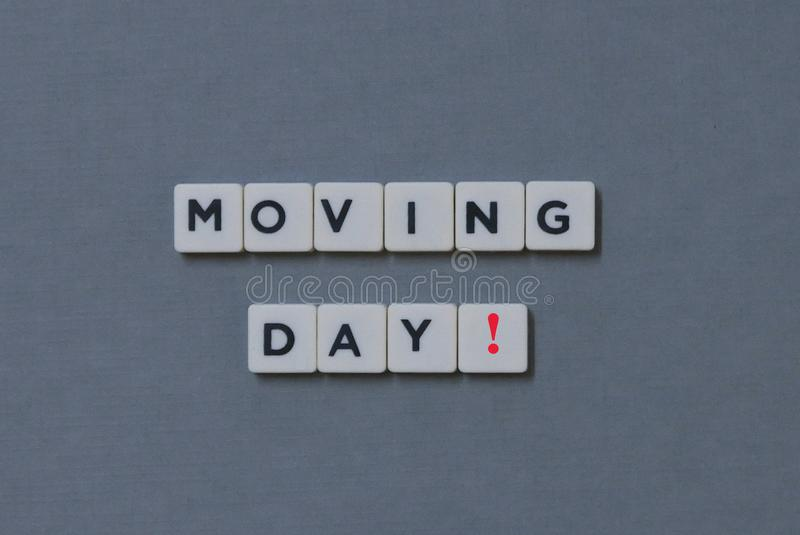 ' Moving Day! ' word made of square letter word on grey background. House, home, package, object, delivery, move, transport, storage, box, relocation stock images