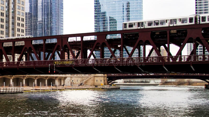 Moving brown line elevated el train, part of Chicago`s iconic transit system, passing over Chicago River at Wells Street. Brown line el train moving quickly stock photo