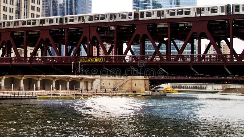 Moving elevated el train, part of Chicago`s iconic transit system, passing over Chicago River where Water Taxi transports commuter. Train moving quickly along stock image