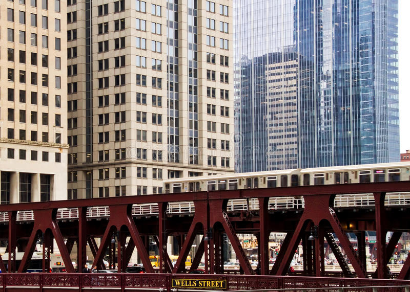 Moving elevated el train, part of Chicago`s iconic transit system, crosses Wells Street bridge over the Chicago River in the Loop. Train moving quickly along stock image