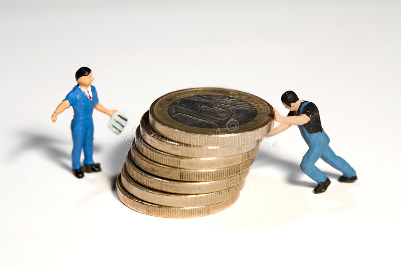 Moving The Euro. Two miniature workmen figurines moving a pile of Euro coins with their hands royalty free stock photos