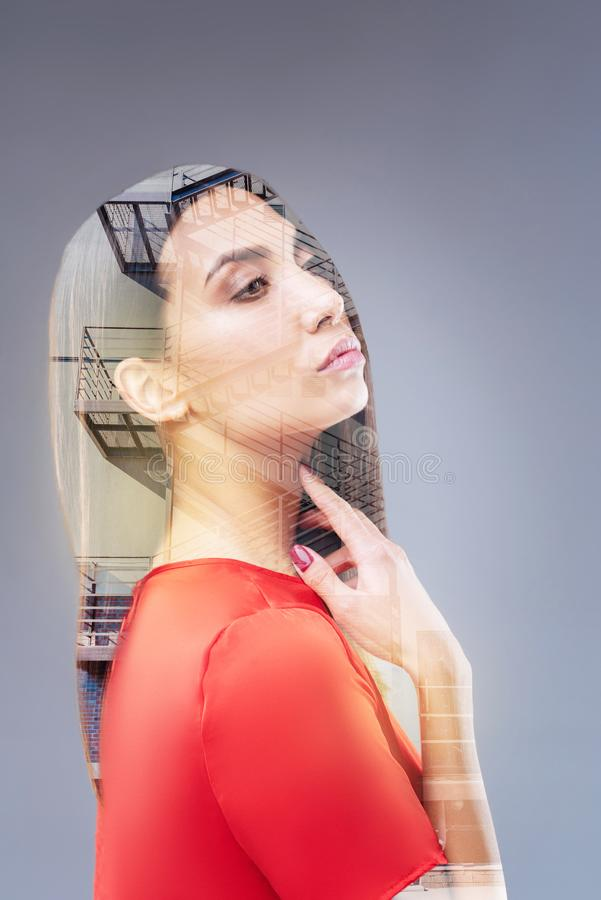 Charming thoughtful woman evaluating her idea. Moving forward. Wistful gorgeous nice woman looking confident while creating future and touching her neck stock images