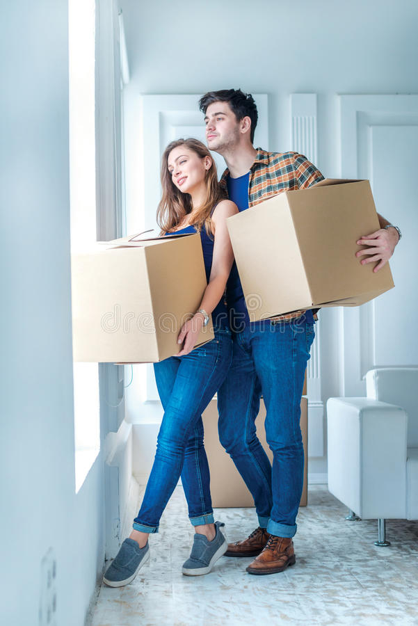 Moving home and repair of a new life. Couple in love pulls thing. S out of boxes for moving while men and women sitting among the boxes in an empty apartment royalty free stock photo