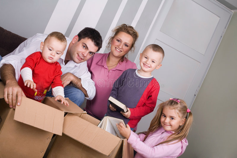 Moving house. Young couple with children moving house royalty free stock photography