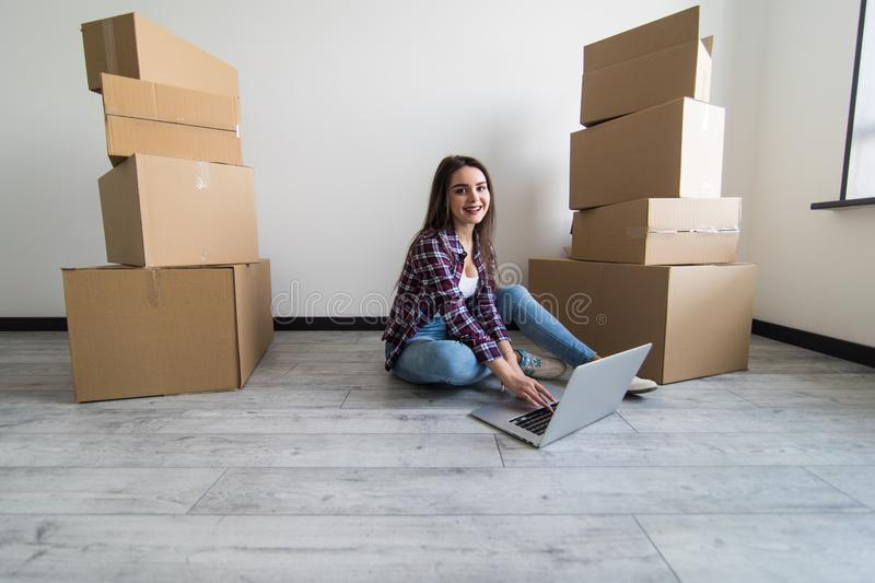 Moving house concept. Young woman relaxing on floor searching on computer in new home. royalty free stock photos