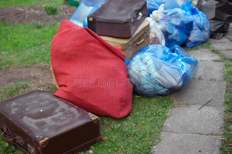 Old unwanted goods and suitcases thrown away. Moving the house, old unwanted goods and suitcases thrown away, outdoor shot stock images