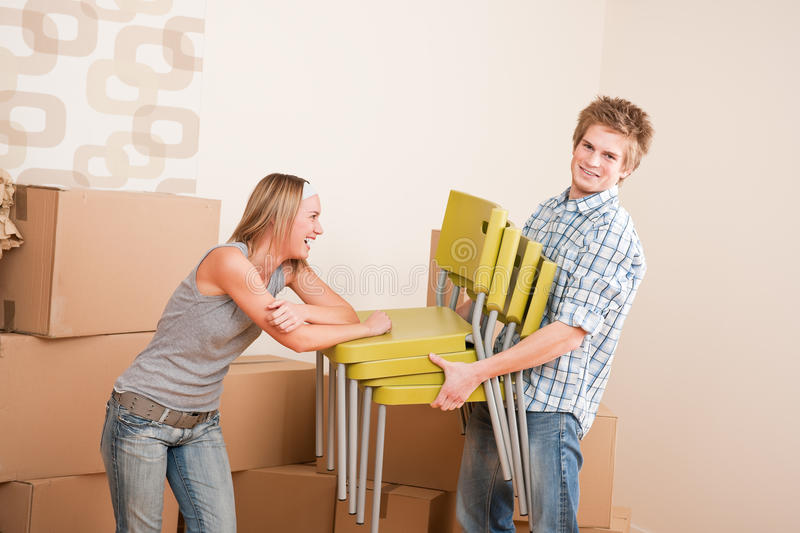 Moving house: Young couple with box and chair. In new home stock photo