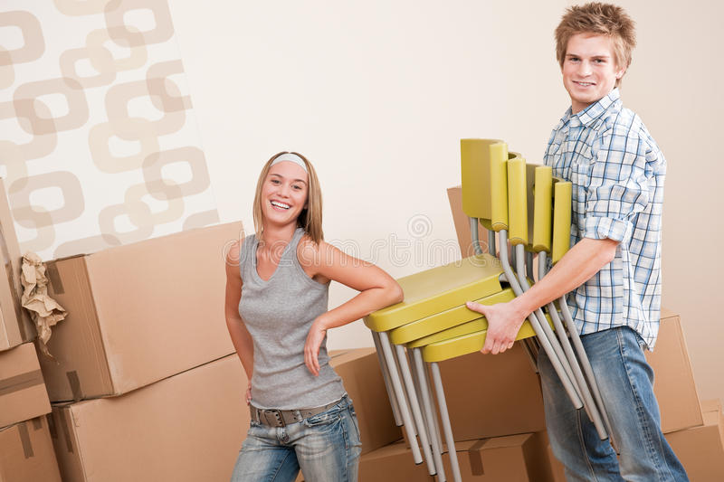 Moving house: Young couple with box and chair. In new home stock image