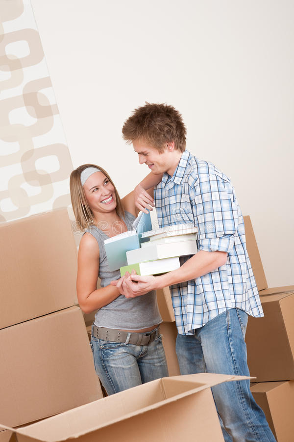 Moving house: Young couple with box in new home. New house: Young couple with box in new home unpacking book stock photo