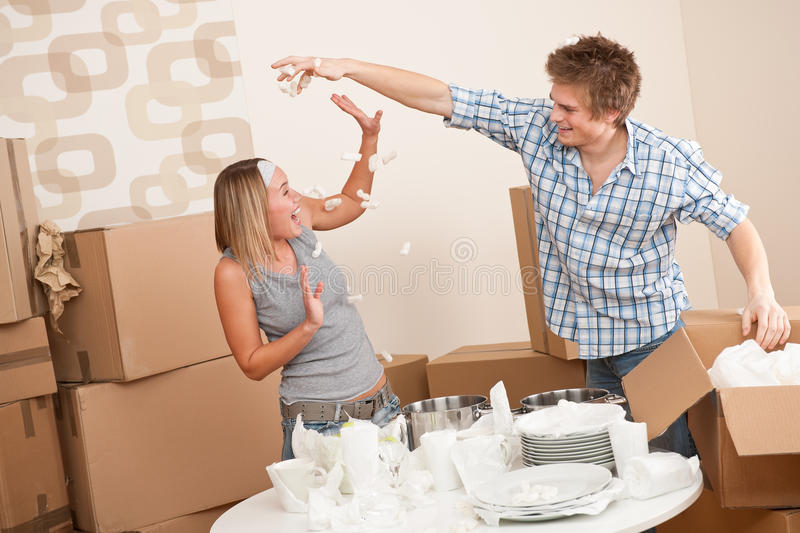 Moving house: Young couple having fun. While unpacking box with kitchen dishes stock photography