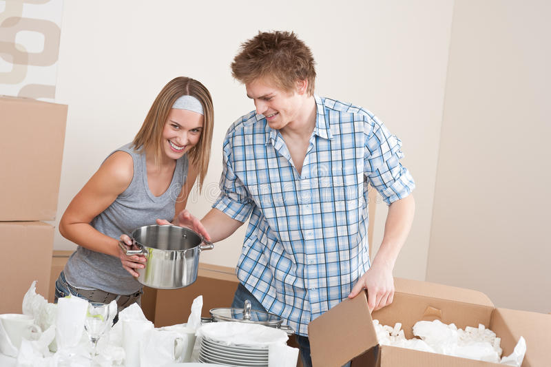 Moving house: Young couple unpacking. Kitchen dishes, pots, pans, in new home stock photos