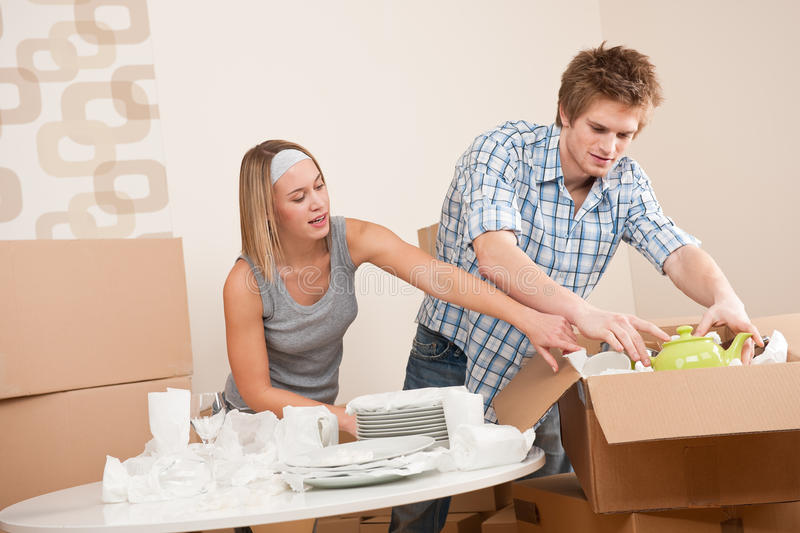 Moving house: Young couple unpacking dishes. Moving house: Young couple unpacking kitchen dishes, pots, pans, in new home royalty free stock photography