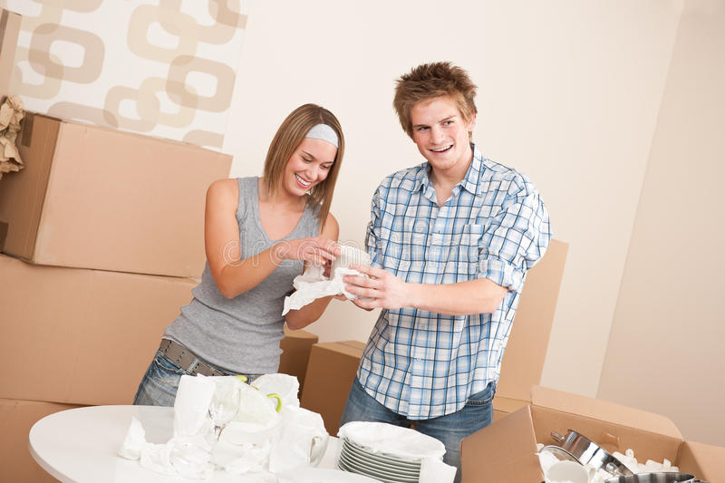 Moving house: Young couple unpacking dishes. Moving house: Young couple unpacking kitchen dishes, pots, pans, in new home royalty free stock image