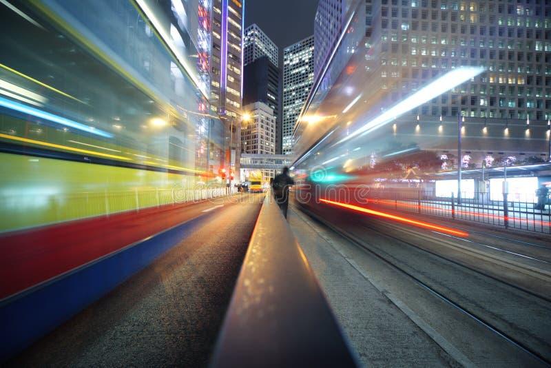 Moving lights background. Fast moving bus lights blurred over modern city background