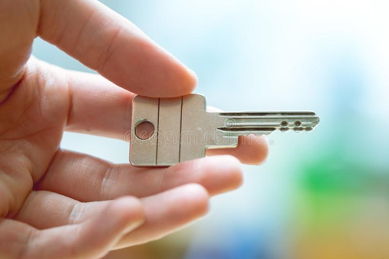 Moving into a new home: Close up of a hand holding a key. Property and real estate. Holding a house key in the hand: New home and property estate owner real rent royalty free stock photo