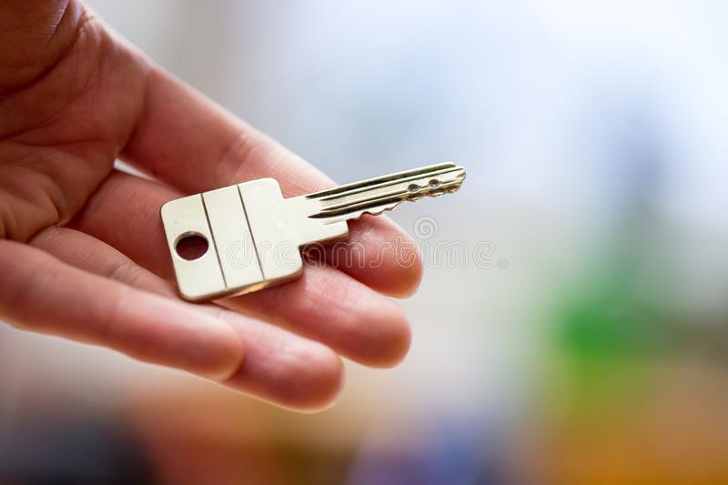 Moving into a new home: Close up of a hand holding a key. Property and real estate. Holding a house key in the hand: New home and property estate owner real rent royalty free stock photos