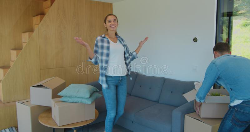 Moving into a new house. Happy couple holding a cardboard box and goes to a new home. Smiling couple hold boxes in new stock image