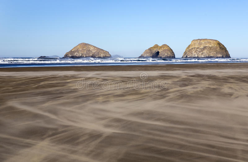 Moving Sands Across the Beach. Winds blow dry sand swiftly across the beach towards the Three Monuments along the Oregon Coast stock photos