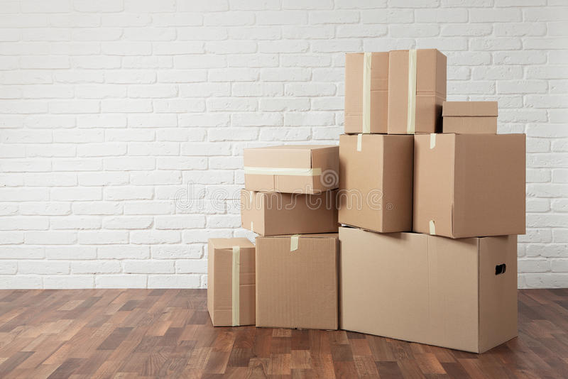Moving in. Stack of cardboard boxes in the empty room with copy space stock photography