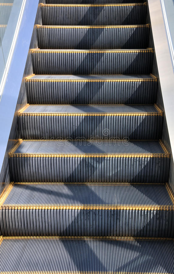 Moving staircase. Under sunshine, shown as structure of construction or architecture, and repeat composition and shape, or industrial concept in featured royalty free stock photography