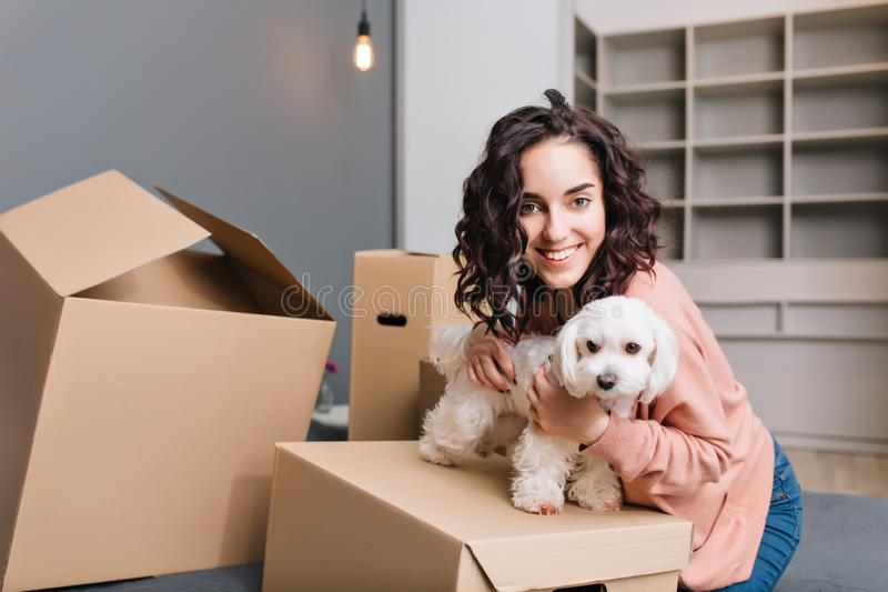 Moving to new apartment of young pretty woman with little dog. Chilling on bed surround carton boxes with pet, smiling stock photography