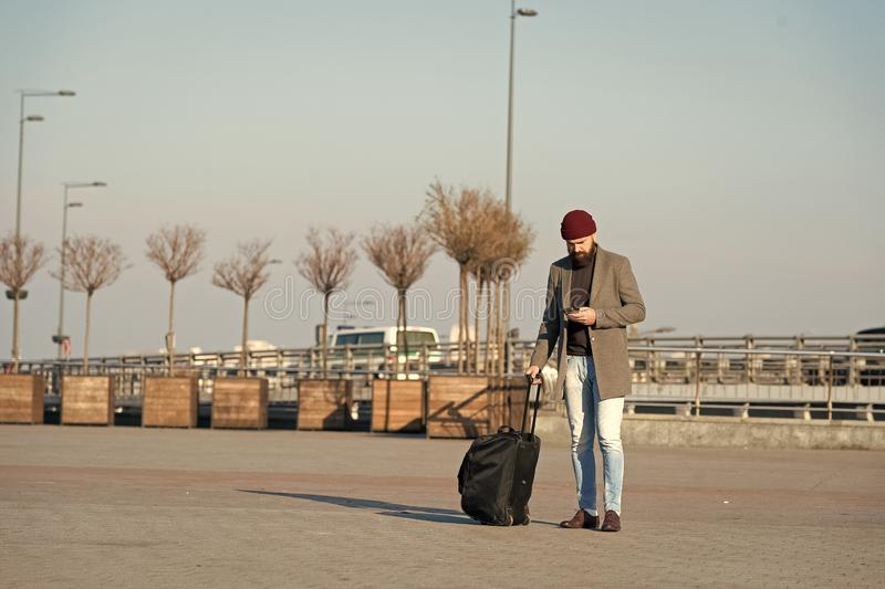 Moving to new city alone. Man bearded hipster travel with luggage bag on wheels. Traveler with suitcase arrive airport. Railway station urban background stock photos