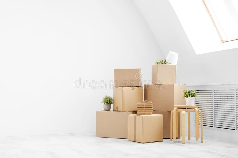 Moving to a new home. Belongings in cardboard boxes, books and green plants in pots stand on the gray floor against the stock photos