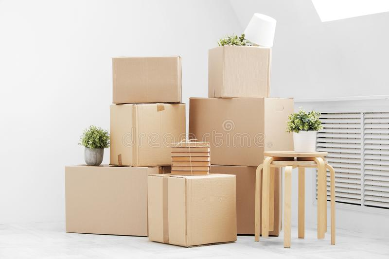 Moving to a new home. Belongings in cardboard boxes, books and green plants in pots stand on the gray floor against the stock images