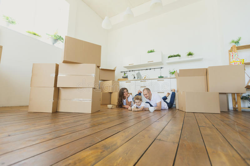 Moving to a new home. Happy family with cardboard boxes. Moving to a new home. Happy family lying on floor after buying new house royalty free stock photo