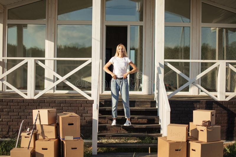 Moving to new home. woman starting new life. Cardboard Boxes near stair royalty free stock photos